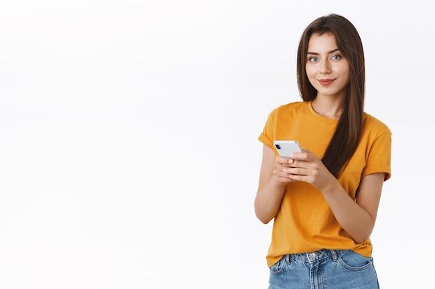노란색 티셔츠를 입은 행복하고 건방진 자신감 있는 소녀, 스마트폰 웃는 자신감 넘치는 카메라, 메시징, 모바일 애플리케이션 사용, 온라인 쇼핑 또는 인터넷 검색, 흰색 배경 서