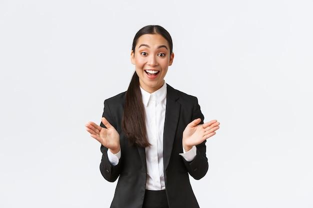 Счастливая довольная азиатская женщина-бизнесвумен реагирует на отличные новости, поднимает руки, аплодирует и поздравляет с большой продажей, хвалит члена команды. веселый предприниматель в костюме радуется