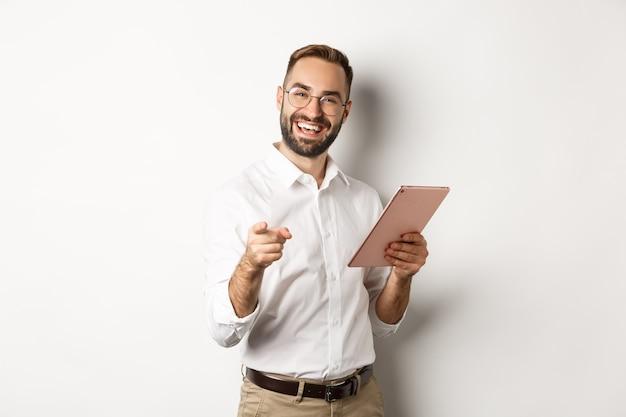Capo felice e soddisfatto che elogia il buon lavoro, legge sulla tavoletta digitale e indica la fotocamera, in piedi