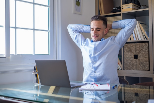 Счастливый довольный кавказский мужчина отдыхает в домашнем офисе, сидит с ноутбуком, держится за руки за головой, мечтательный молодой мальчик расслабляется после завершения работы, чувствует душевное спокойствие, отводит взгляд, мечта, думает о концепции будущего успеха