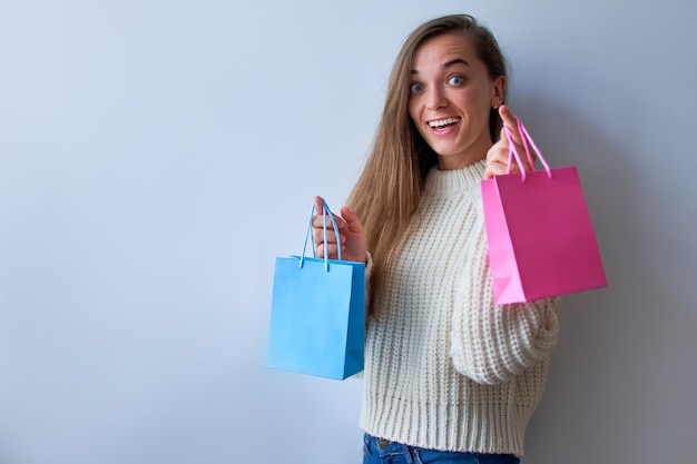 Happy satisfied cheerful suprised joyful woman shopaholic with colored bright paper gift bags.