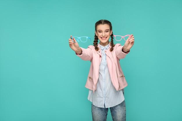 Счастливая довольная девушка в повседневном или хипстерском стиле, прическа косичка, стоит, держит голубые и розовые очки и с зубастой улыбкой смотрит в камеру, съемка в закрытой студии, изолированная на зеленом фоне