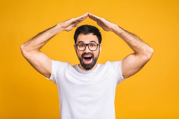 Счастливый довольный красивый молодой человек, стоящий с руками жест крыши на голове и смотрящий с зубастой улыбкой. студийный снимок