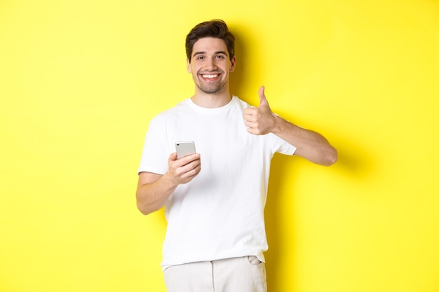 Happy satisfied man holding smartphone, showing thumb up in approval, recommend something online, standing over yellow background