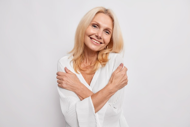 Happy satisfied middle aged woman embraces herself smiles gently shows white teeth tilts head dressed in silk blouse isolated over white wall has romantic tender expression needs love