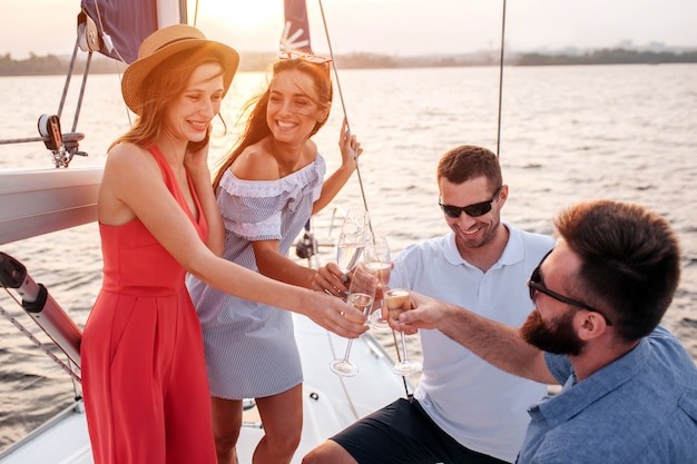 Happy and satisfied people stands on board of yacht. women reaches with glass of champaigne to men. brunette is talking and looking at another young women. men wear sunglasses.