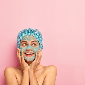 Happy satisfied woman touches both cheeks with hands, wears blue facial scrub on face, stands bare alone, being deep in thoughts, has glad expression, poses over rosy wall