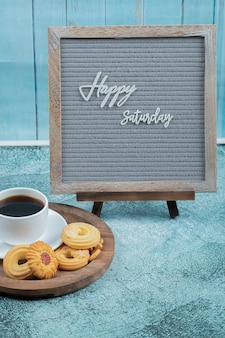 Happy saturday embedded on grey background with cookies and a cup of drink around