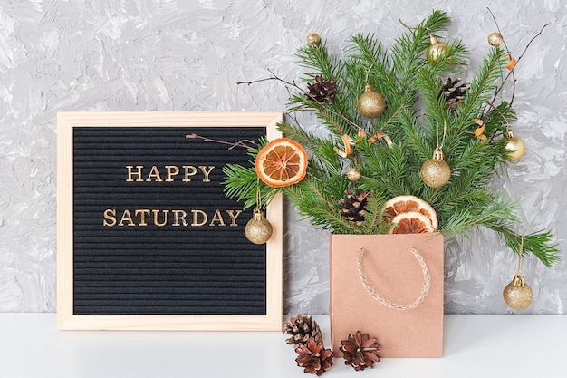 Happy saturday text on black letter board and festive bouquet of fir branches with christmas decor in craft package on table.