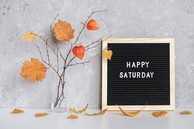Happy saturday text on black letterboard and bouquet of branches with yellow leaves
