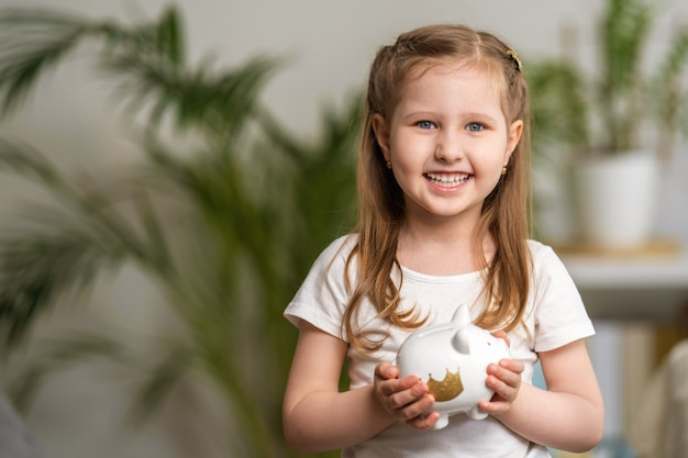 Happy savings. a little cute girl with a piggy bank at home