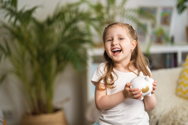 Happy savings. little laughing girl with a piggy bank, at home.