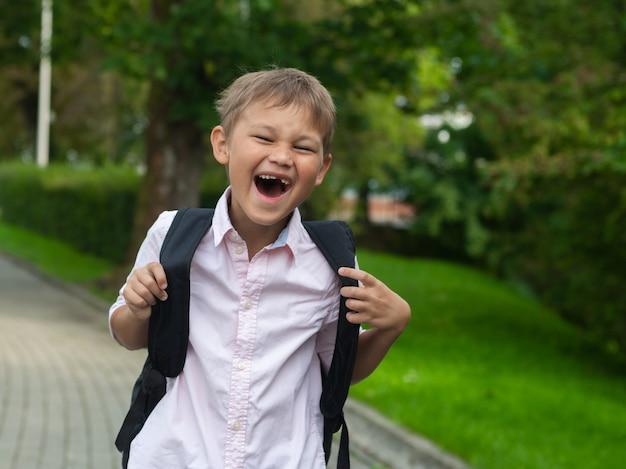 彼のバッグを押しながら笑みを浮かべて幸せな学校の男の子