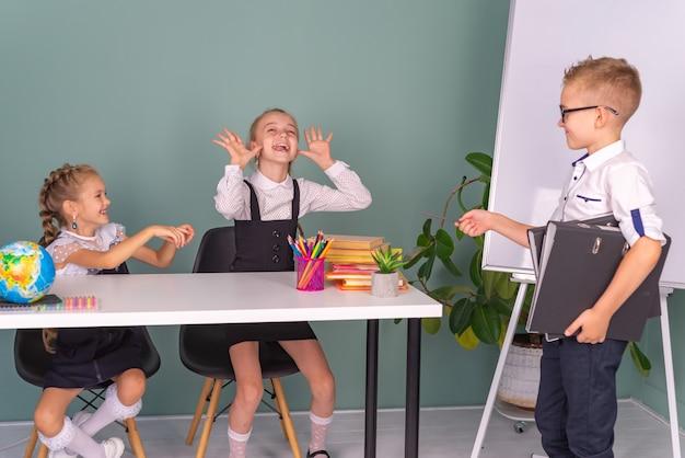 家で一緒に宿題をしている幸せな学校の子供たちの男の子と女の子