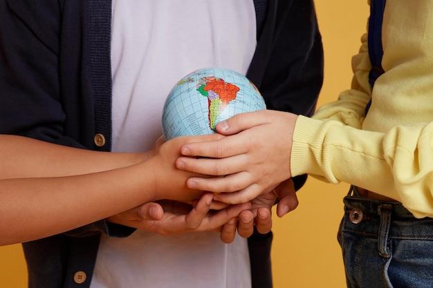 Счастливые школьные друзья держат земной шар