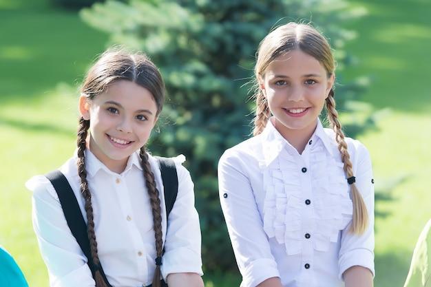 교복을 입은 행복한 학교 친구들은 방과 후 야외에서 화창한 날을 즐깁니다.