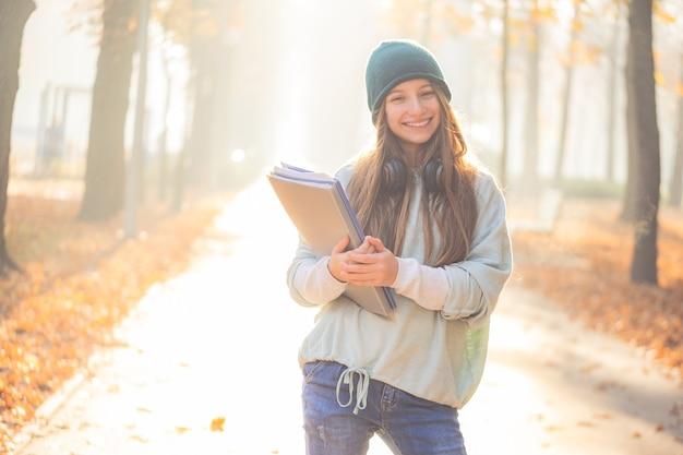 秋の公園でフォルダーを保持している幸せな女子高生