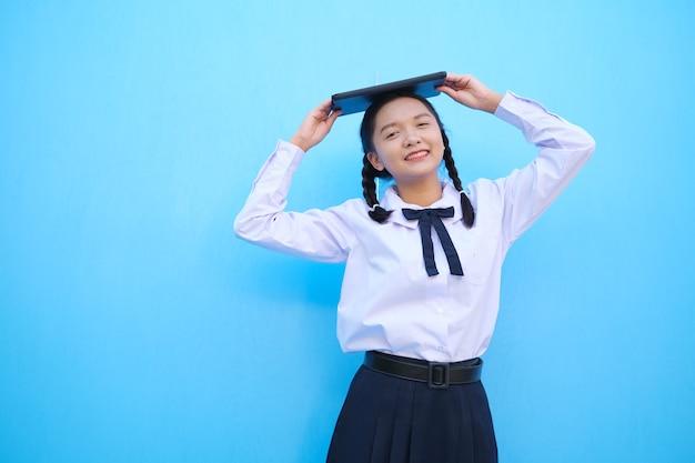 Азиатская девушка с ноутбуком на синем фоне