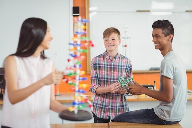 幸せな学校の子供たちが実験室で分子モデルを実験