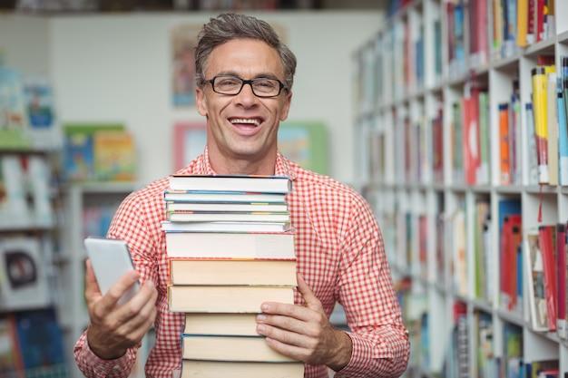 図書館で携帯電話を使用しながら本のスタックを保持している幸せな学校の先生