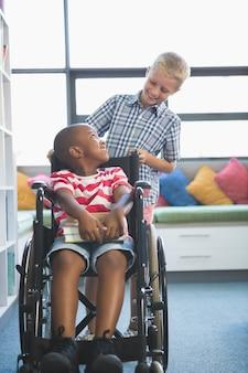 車椅子で彼の友人を運ぶ幸せな少年