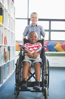Happy schoolboy carrying his friend in wheelchair