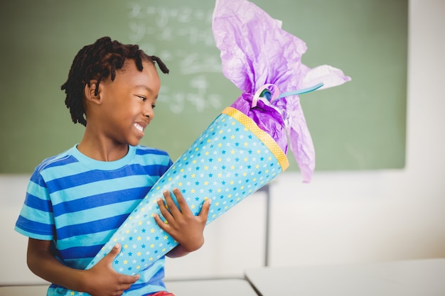 Happy schoolboy holding gift in classroom