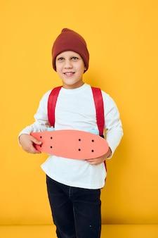 彼の手の孤立した背景に赤い帽子のスケートボードで幸せな男子生徒