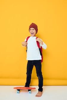 白いセータースケートボードエンターテインメント黄色の背景で幸せな男子生徒