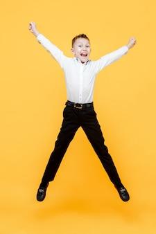 幸せな少年が喜びのためにジャンプします。黄色の表面で分離されました。幸福、活動および子供の概念。