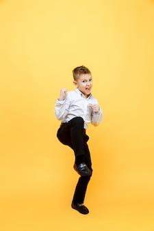Happy schoolboy jumping for joy. isolated over yellow surface. happiness, activity and child concept.