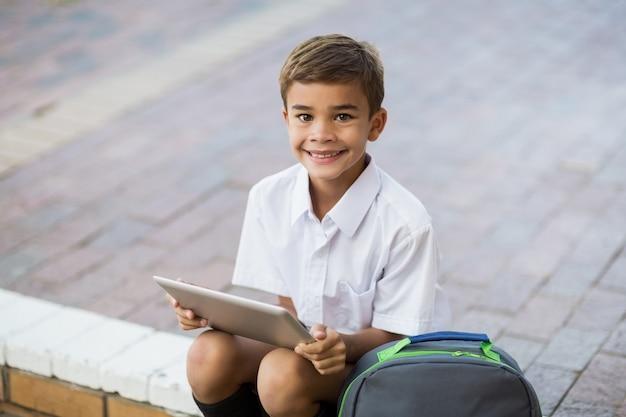 Happy schoolboy sitting in campus and using digital tablet
