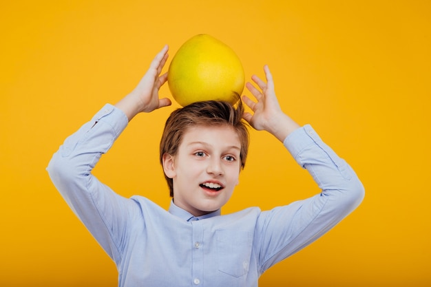 Happy schoolboy in t shirt holding large pomelo on head