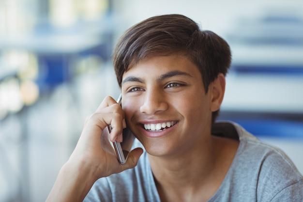 Счастливый школьник разговаривает по мобильному телефону в классе