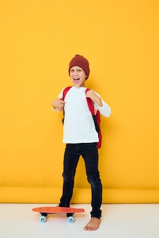 Happy schoolboy in a white sweater skateboard entertainment yellow color background