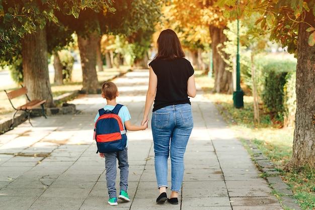 Счастливый школьник с рюкзаком и его мама
