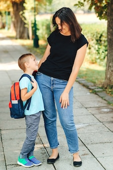 Happy schoolboy with a backpack and his mother