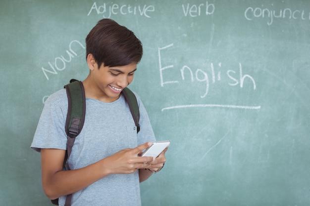 Счастливый школьник с рюкзаком, используя мобильный телефон в классе