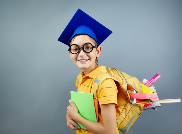 Happy schoolboy with black glasses and graduation cap