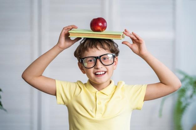 Счастливый школьник с книгами и яблоком в руках. обратно в школу.