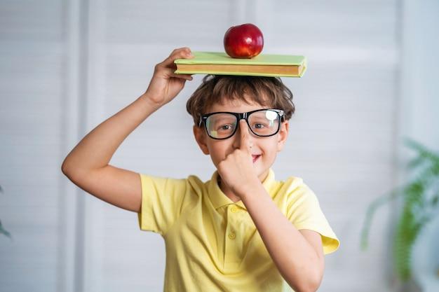 Счастливый школьник с книгами и яблоком в руках
