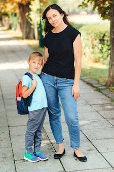 学校に行く途中で母親と一緒に幸せな男子生徒。クラスの初日。