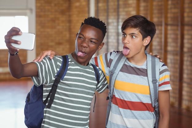 キャンパス内の携帯電話でselfieを取って幸せな男子生徒