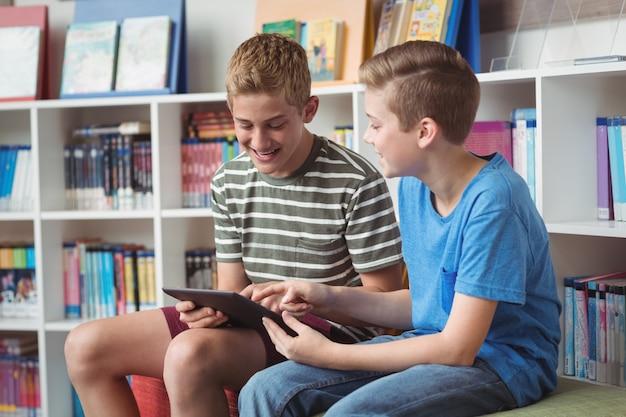 Happy schoolboys using digital tablet in library