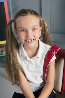 Happy schoolchild in the classroom with big backpack