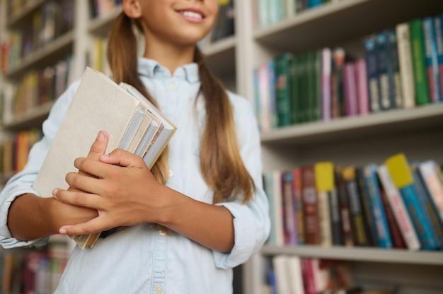 Счастливый школьник с книгами, стоя в библиотеке
