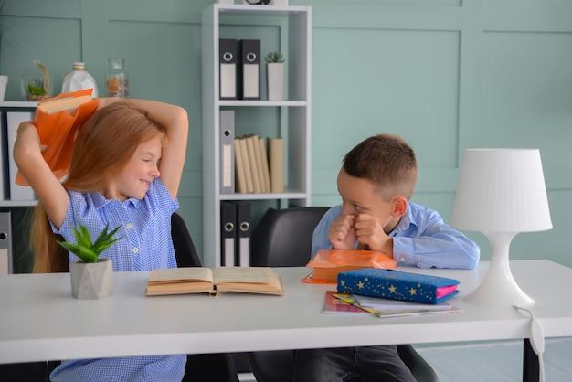 幸せな小学生のクラスメートの男の子と女の子が学校で一緒に勉強します