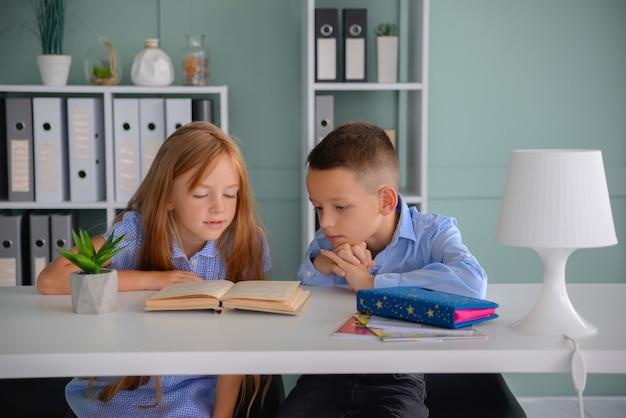 Happy schoolchildren classmates boy and girl study together at school