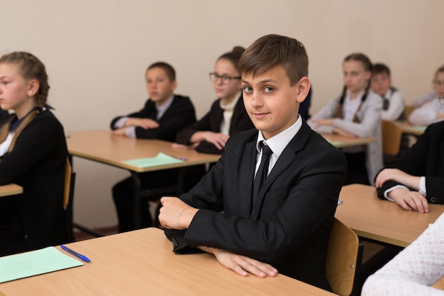 幸せな学童は教室の机に座っています