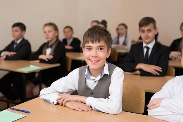 교실에서 책상에 앉아 행복한 학생